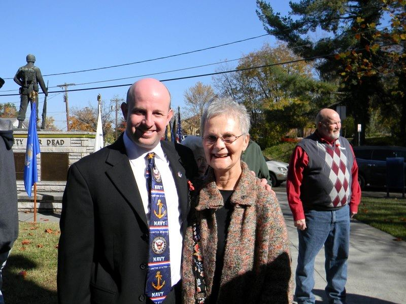 Man stands next to and with arm around the shoulders of a smiling woman, outside in back of memorial